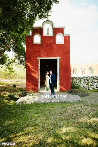 Portrait of bride and groom standing in front of chapel at tropical resort after wedding ceremony