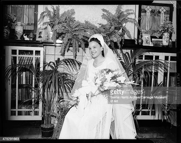 Portrait of bride Dorothy Jackson wearing gown with sweetheart neckline seated in domestic interior Pittsburgh Pennsylvania July 1946
