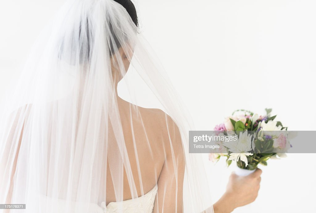 Portrait of bride in veil holding bouquet : Stock Photo