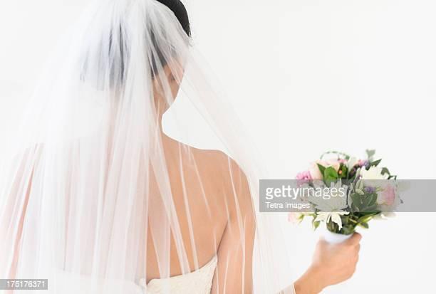 Portrait of bride in veil holding bouquet