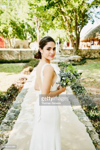 Portrait of bride in wedding gown walking to outdoor ceremony at tropical resort
