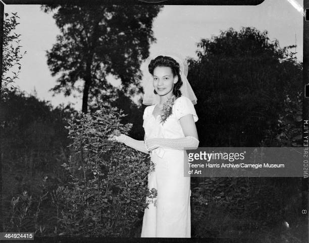 Portrait of bride Mary Jane Mitchell Page wearing white pique dress with short sleeves sweetheart neckline and fingerless lace gloves standing beside...