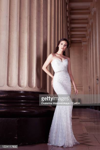 portrait of bride standing in corridor - wedding dress stock pictures, royalty-free photos & images