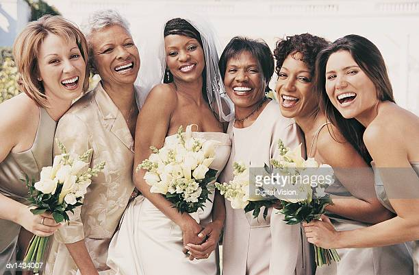 portrait of bride standing with mothers and her bridesmaids - bridesmaid stock pictures, royalty-free photos & images