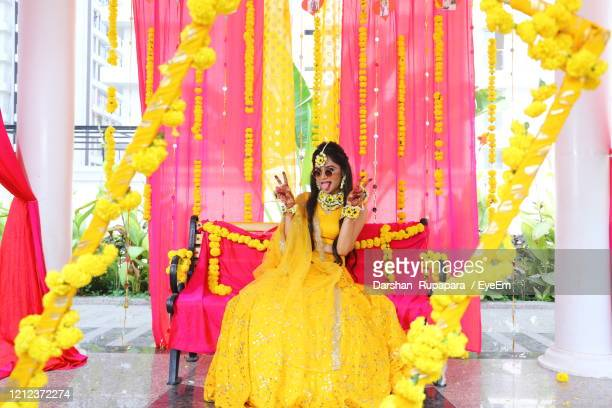 portrait of bride wearing sunglasses gesturing while sitting on chair at haldi ceremony - indian wedding stock pictures, royalty-free photos & images