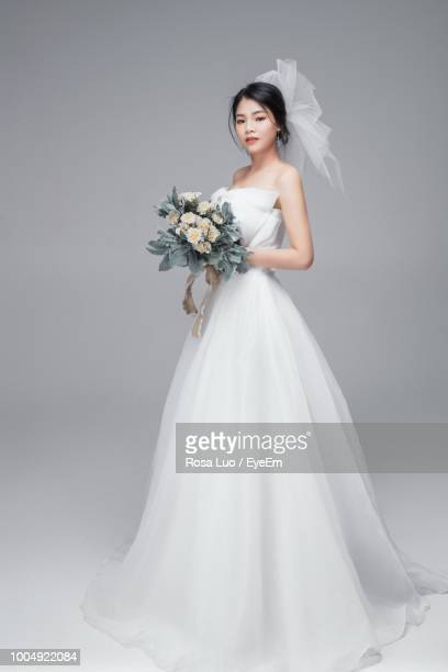 portrait of bride with bouquet standing against gray background - ウェディングドレス ストックフォトと画像
