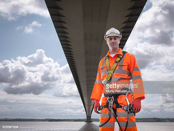 Portrait of bridge worker under suspension bridge. The Humber Bridge, UK was built in 1981 and at the time was the worlds largest single-span suspension bridge