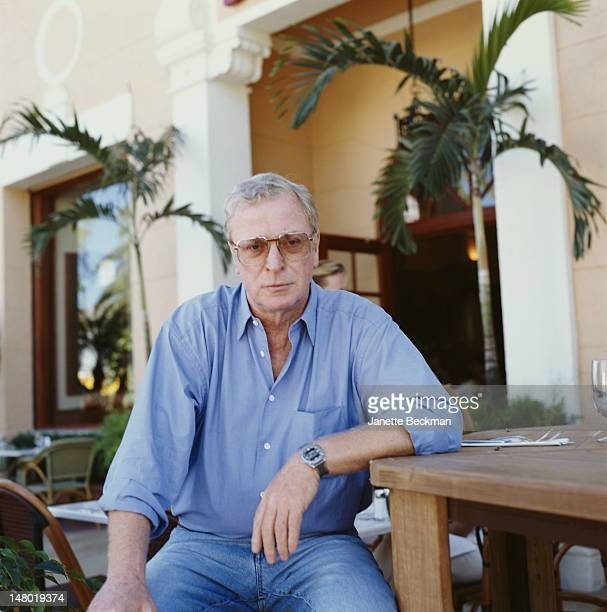 Portrait of British actor Michael Caine as he poses at an outdoor restaurant, Miami, Florida, 2001.