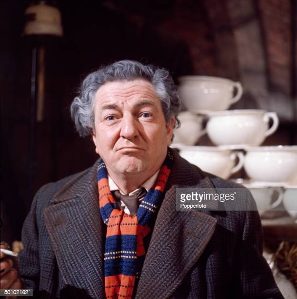Portrait of British actor Rupert Davies posed wearing an overcoat and scarf on the set of the television drama 'The OneEyed Monster' in 1966