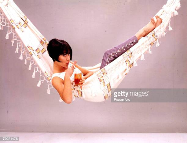 1965 A portrait of British Actress Amanda Barrie relaxing with a drink in a hammock