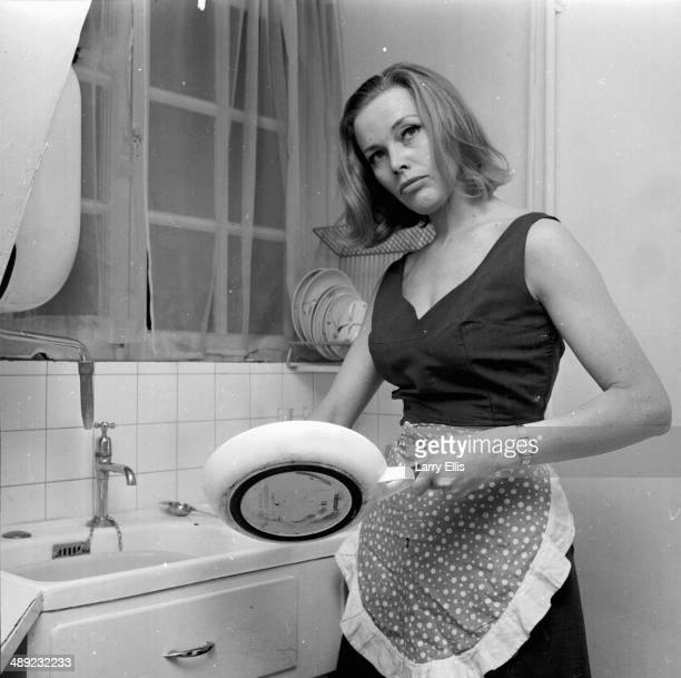 Portrait of British actress Honor Blackman washing dishes 1964