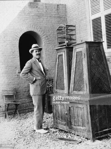 Portrait of British archaeologist Hward Carter as he stands with arms akimbo outside a building next to a cabinet and a birdcage Egypt early 1920s