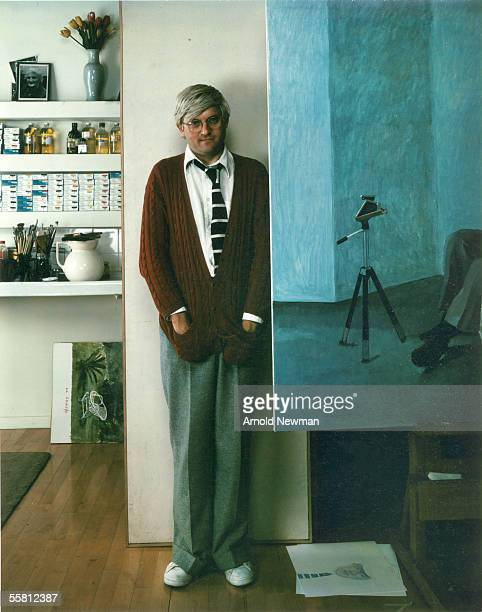 Portrait of British artist David Hockney as he poses hands in the pocket of his cardigan next to one of his paintings London England May 28 1978