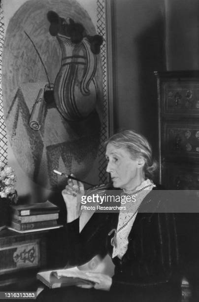 Portrait of British author Virginia Woolf as she smokes a cigarette holder, an open book on her lap, London, England, 1939. On the wall behind her is...