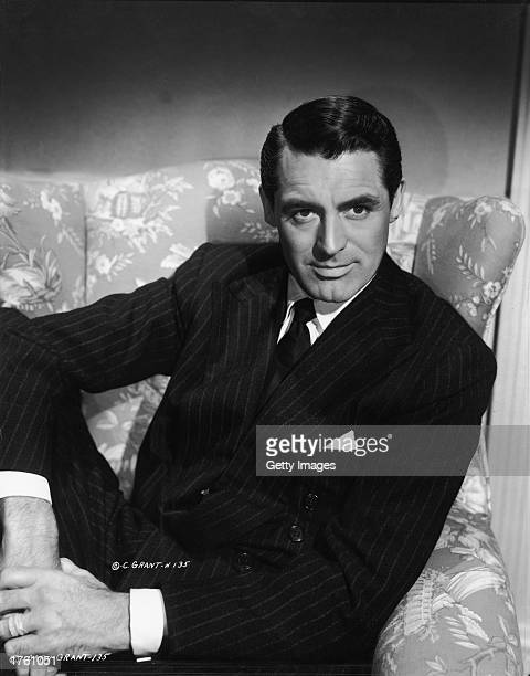 Portrait of British born actor Cary Grant wearing a double breasted pinstripe suit seated in an armchair 1940s