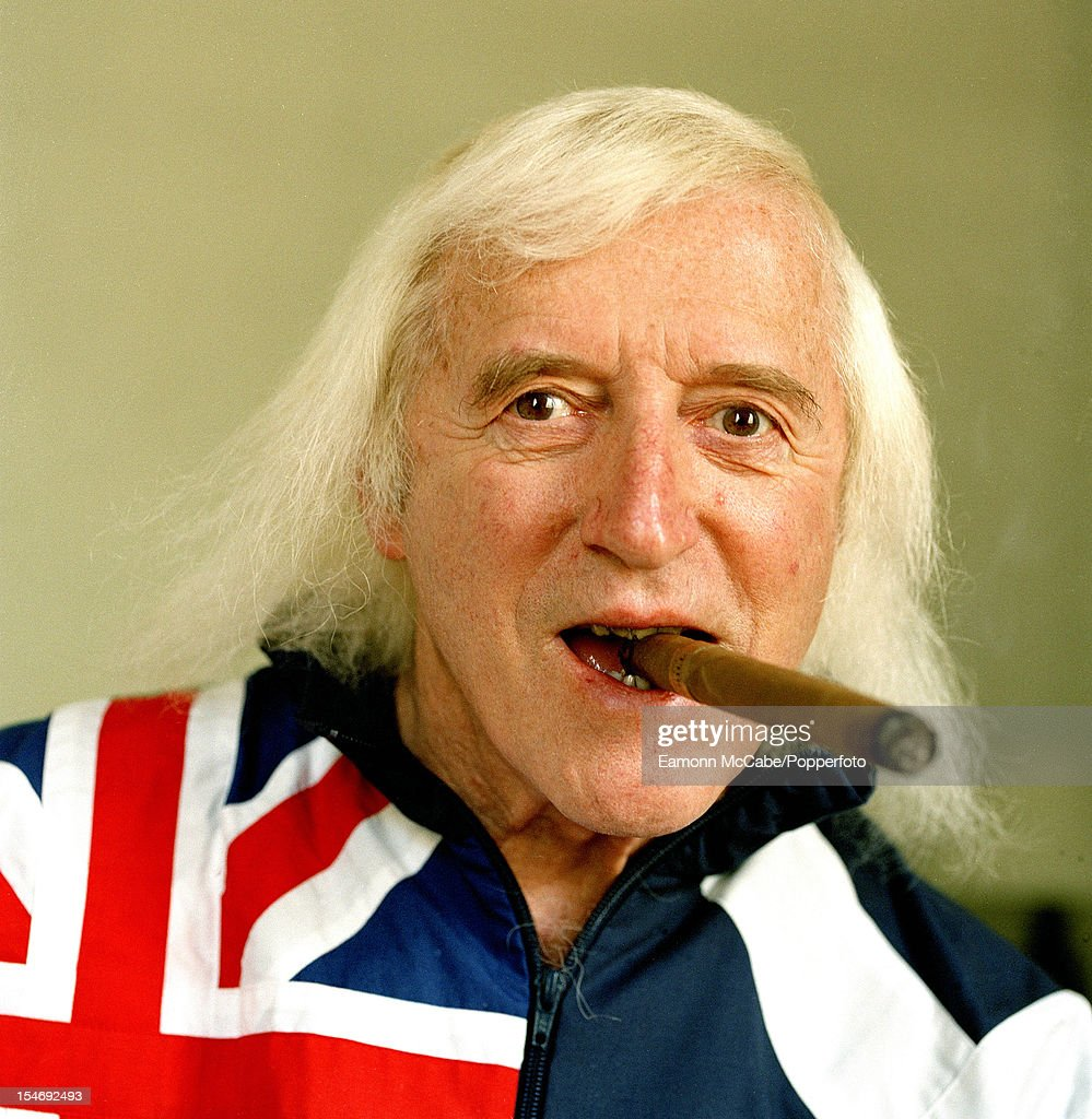 Portrait of British disc jockey, television broadcaster and charity fundraiser Jimmy Savile smoking a cigar, UK, circa 2005.