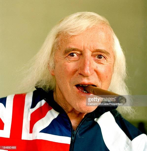 Portrait of British disc jockey television broadcaster and charity fundraiser Jimmy Savile smoking a cigar UK circa 2005