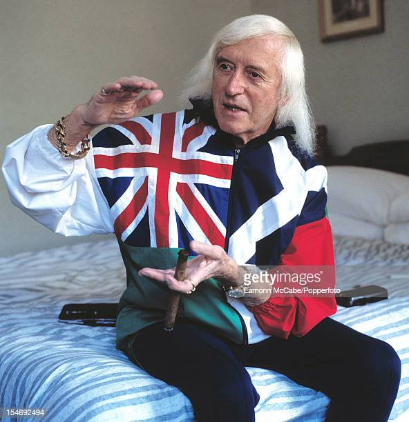 Portrait of British disc jockey television broadcaster and charity fundraiser Jimmy Savile sitting on a bed in a hotel room smoking a cigar UK circa...