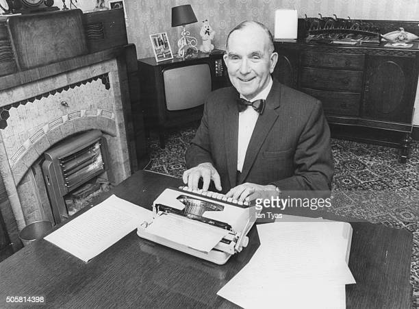 Portrait of British executioner Albert Pierrepoint writing his memoirs at a typewriter in front of a fireplace circa 1973