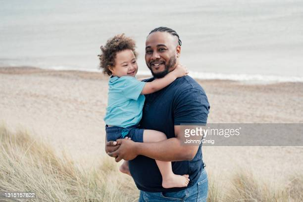 portrait of british father and son vacationing at the beach - genderblend stock pictures, royalty-free photos & images