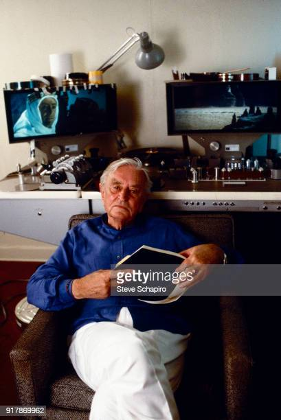 Portrait of British film director David Lean as he holds a notebook, Los Angeles, California, 1988. Behind him is K-E-M flatbed editor that displays...