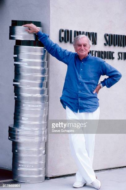 Portrait of British film director David Lean as he poses beside a stack of film canisters outside the Goldwyn Sound Facility, Los Angeles,...
