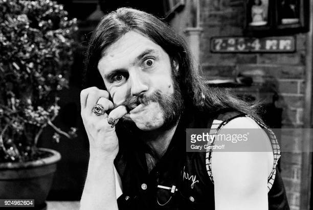 Portrait of British Heavy Metal musician Lemmy , of the group the Motorhead, makes a face with one finger hooked in his mouth as he poses at MTV...