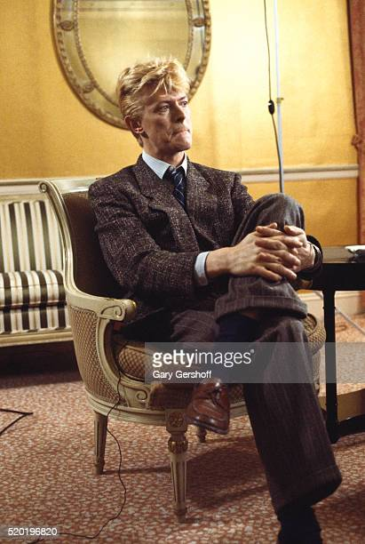 Portrait of British musician and actor David Bowie as he sits crosslegged in an armchair during a interview at the Carlyle Hotel New York New York...