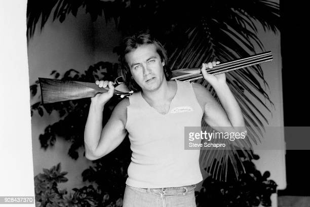 Portrait of British musician and lyricist Bernie Taupin as he poses with a shotgun over his shoulders Los Angeles California April 1980