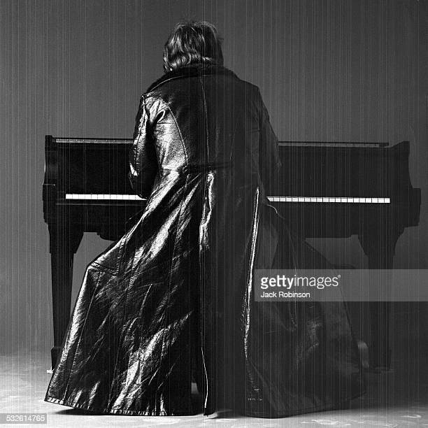 Portrait of British musician Elton John dressed in a leather duster as he plays piano 1970