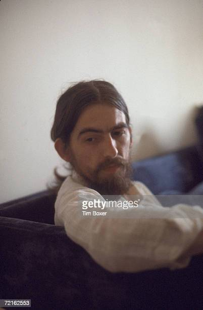 Portrait of British musician George Harrison as he sits on a sofa and looks over his shoulder New York New York May 1970