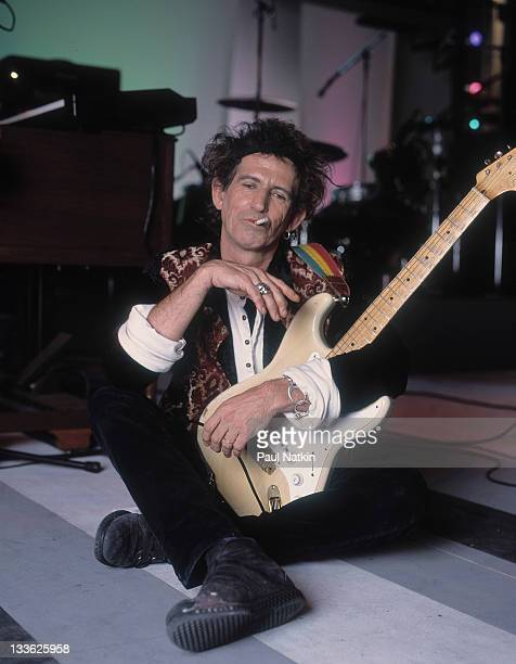 Portrait of British musician Keith Richards as he holds a guitar and sits on stage during the filming of an episode of the PBS television series...