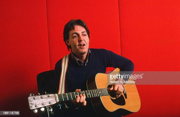 Portrait of British musician Paul McCartney as he plays acoustic guitar against a red background October 7 1984