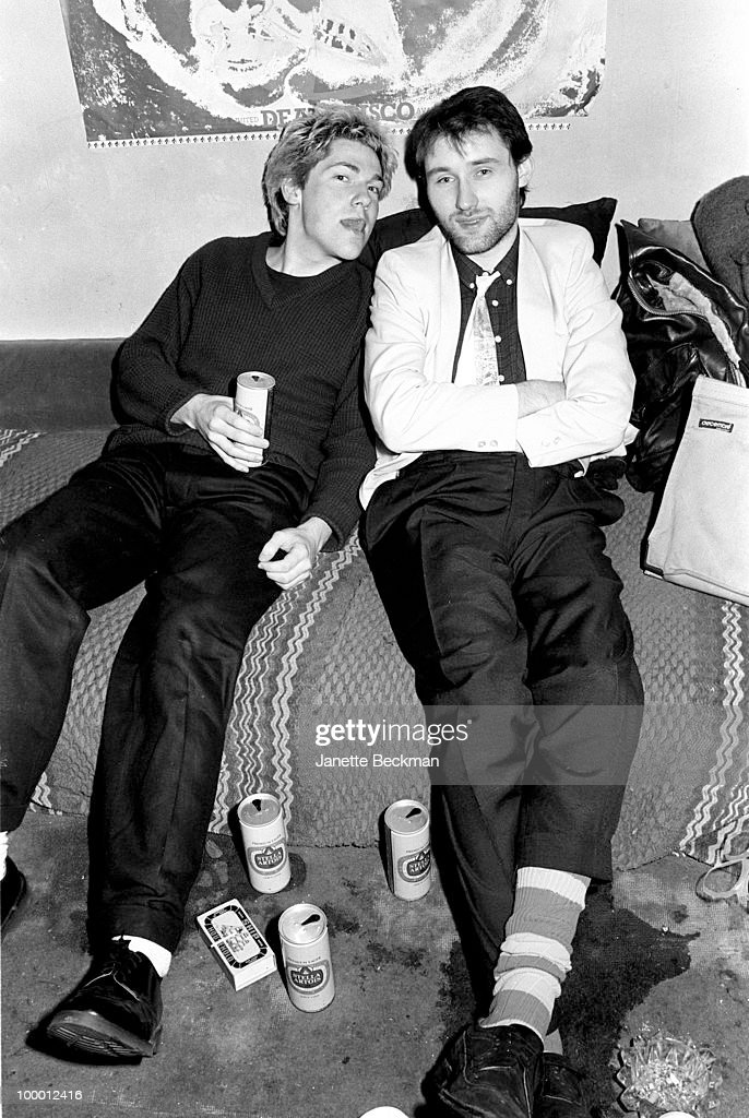Portrait of British musicians Jah Wobble (born John Wardle) (left) and Martin Atkins of the post-punk band Public Image Ltd as sit on a bed in band leader John Lydon's apartment, London, England, 1979.
