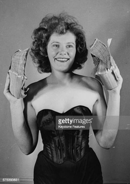 Portrait of British performer Joan Rhodes showing her strength by tearing a phone book apart March 1st 1950