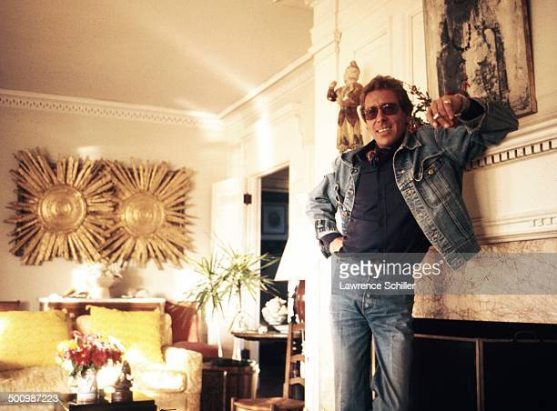 Portrait of British photographer Antony ArmstrongJones 1st Earl of Snowdon a cigarette in his hand as he leans on a fireplace mantel 1974