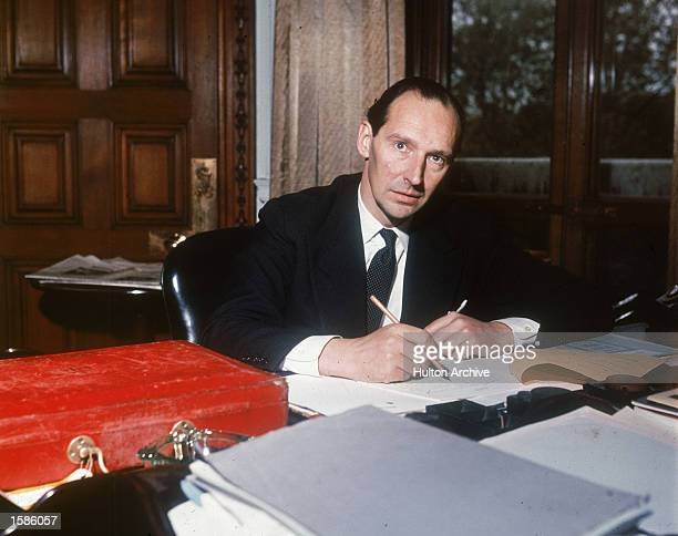 Portrait of British politician David OrmsbyGore sitting at a desk and writing