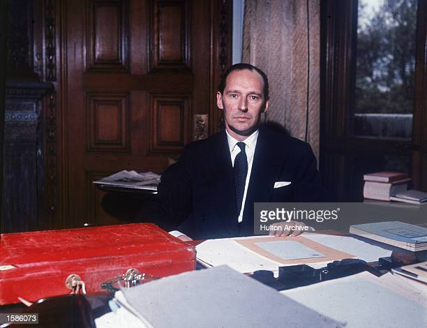 Portrait of British politician David OrmsbyGore sitting at a desk surrounded by documents