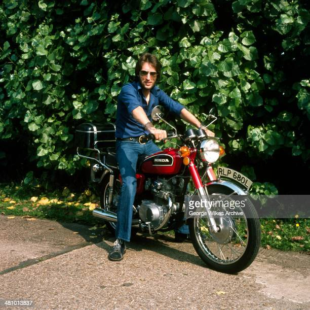 Portrait of British radio disc jockey and broadcaster Johnnie Walker as he poses on a motorcycle, London, England, 1977.