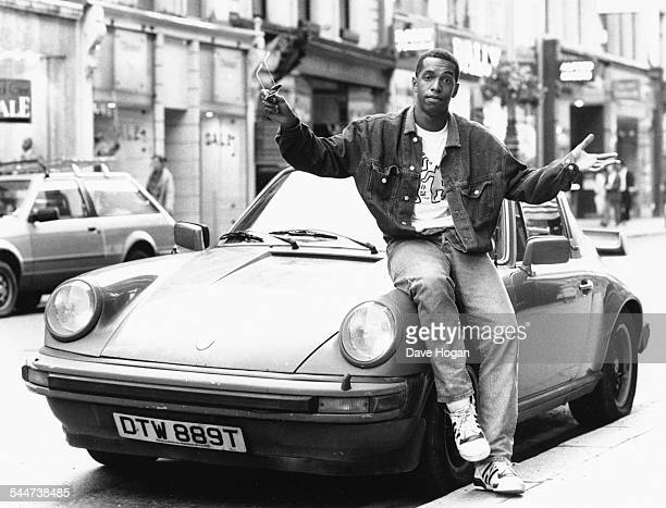 Portrait of British rapper Derek B sitting on the hood of a car July 15th 1988