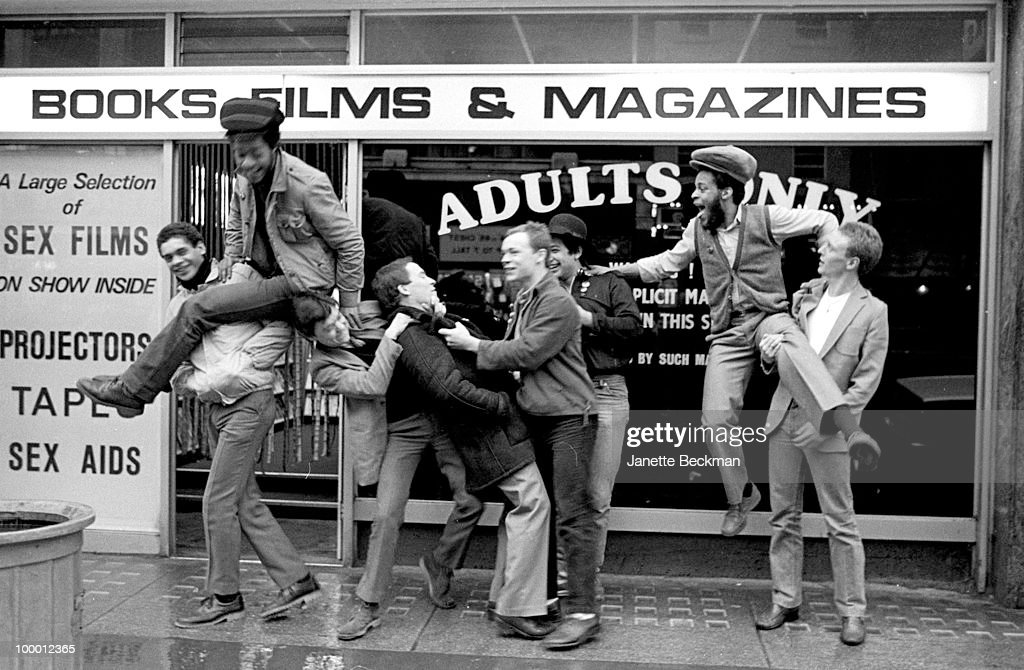 Portrait of British reggae group UB40 as they clown about in front of a sex shop), Brimingham, England, 1981. Pictured are band members Ali Cambell, Robin Cambell, Jimmy Brown, Mickey Virtue, Earl Falconer, Norman Hassan, Astro (born Terence Wilson), and Brain Travers.