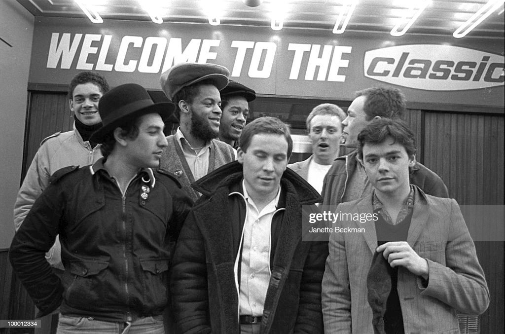 Portrait of British reggae group UB40 as they pose in front of the Classic cinema (at 47 Station Street, later known as the Electric Cinema), Brimingham, England, 1981. Pictured are band members Ali Cambell, Robin Cambell, Jimmy Brown, Mickey Virtue, Earl Falconer, Norman Hassan, Astro (born Terence Wilson), and Brain Travers.