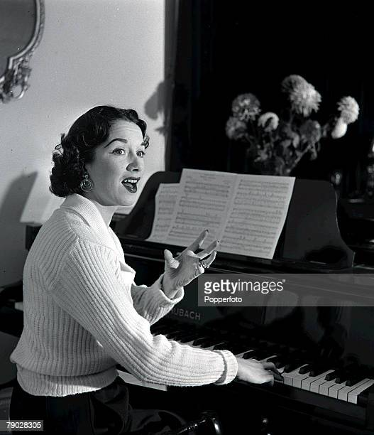 1953 Portrait of British singer and actress Pat Kirkwood rehearsing a song on her piano at her home in London