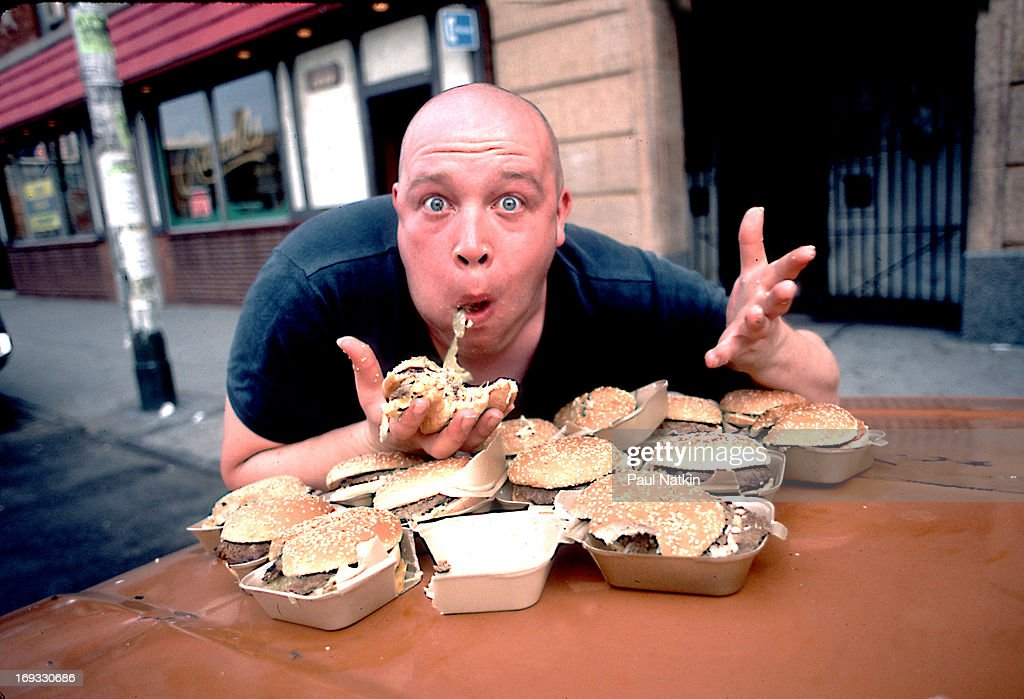 Portrait of British singer Buster Bloodvessel (born Douglas Trendle), of the ska group Bad Manners, as he sits at an outdoor table full of hamburgers, Chicago, Illinois, 1984.