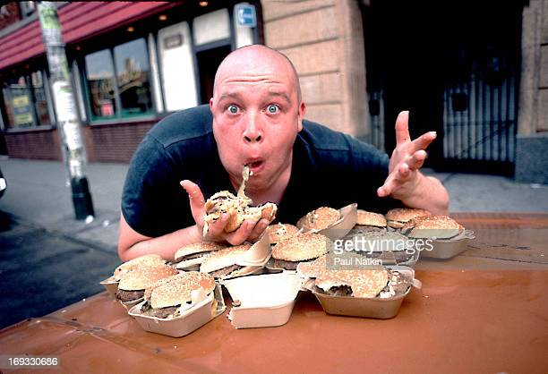 Portrait of British singer Buster Bloodvessel of the ska group Bad Manners as he sits at an outdoor table full of hamburgers Chicago Illinois 1984