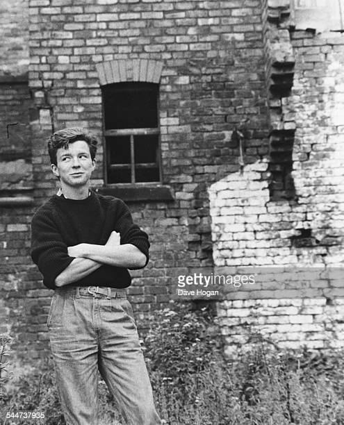 Portrait of British singer Rick Astley in front of a brick wall circa 1985