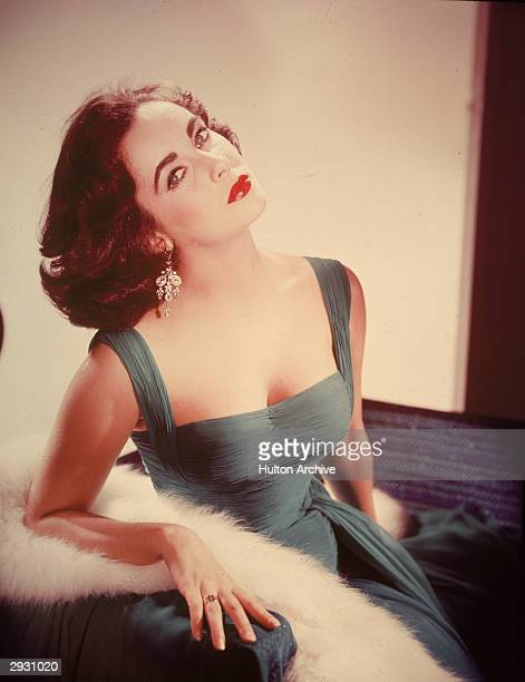 Portrait of Britishborn actor Elizabeth Taylor in a formfitting green dress as she sits with her head tilted back exposing her neck circa 1950s
