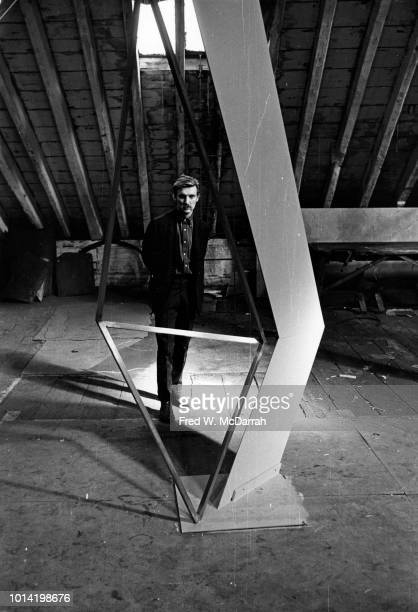 Portrait of Britishborn painter and sculptor Tony Magar seen through a sculpture as he poses in his loft studio New York New York November 20 1965
