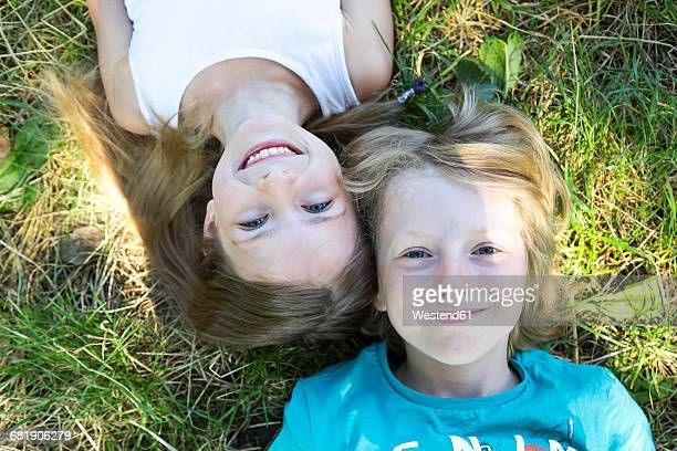 Portrait of brother and little sister lying on a meadow looking up to camera