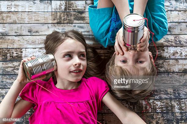 Portrait of brother and little sister playing with tin can phone